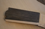 Headstock roughly carved, the cedar top behind
